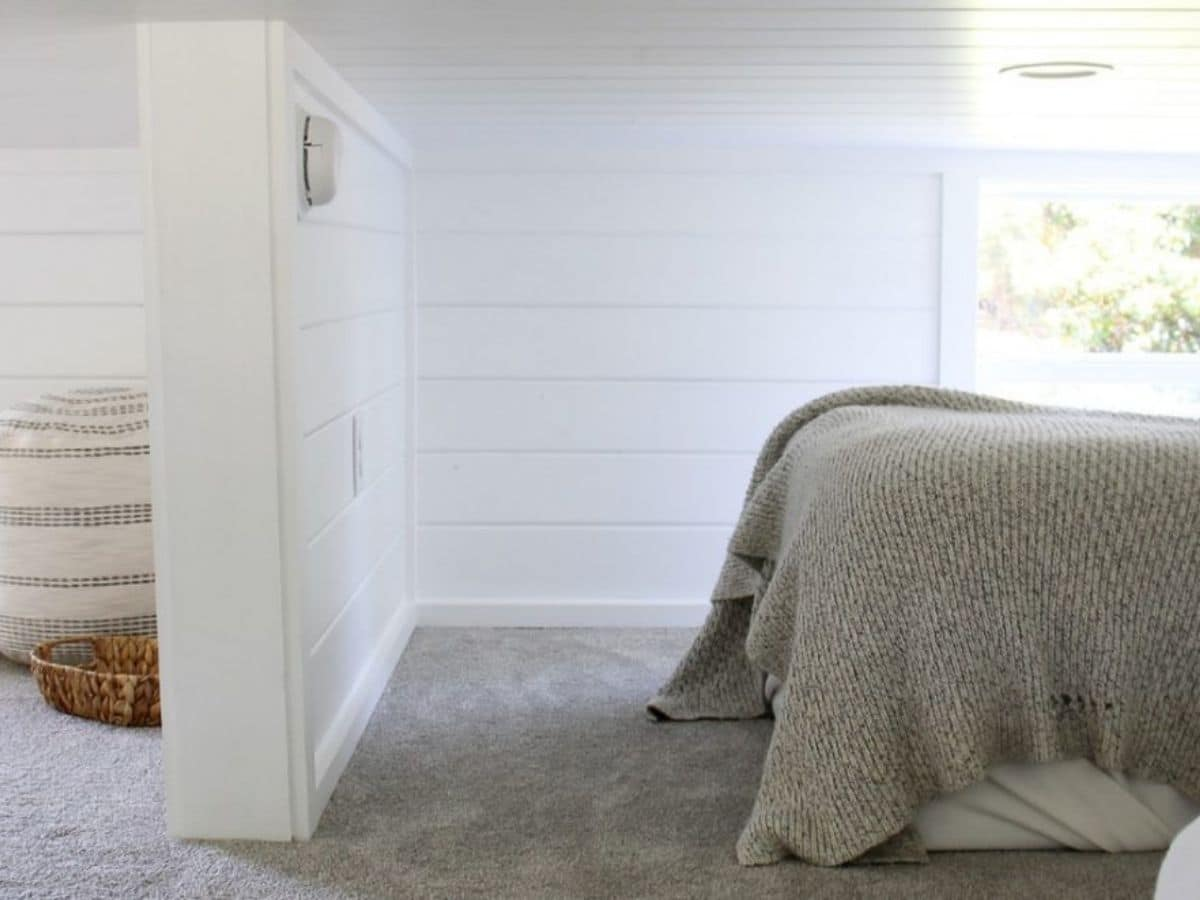 Bed against window in loft with wall divider