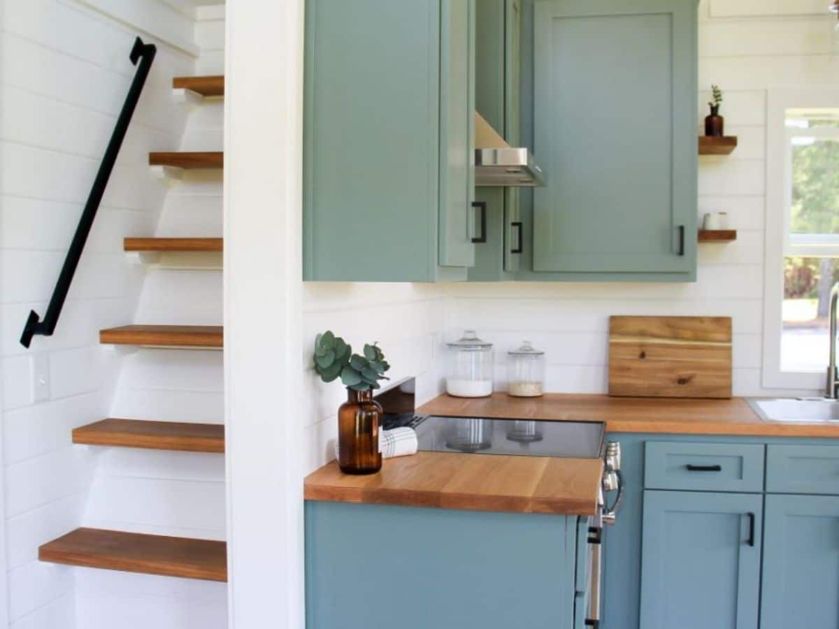 Light teal cabinets next to wall by stairs