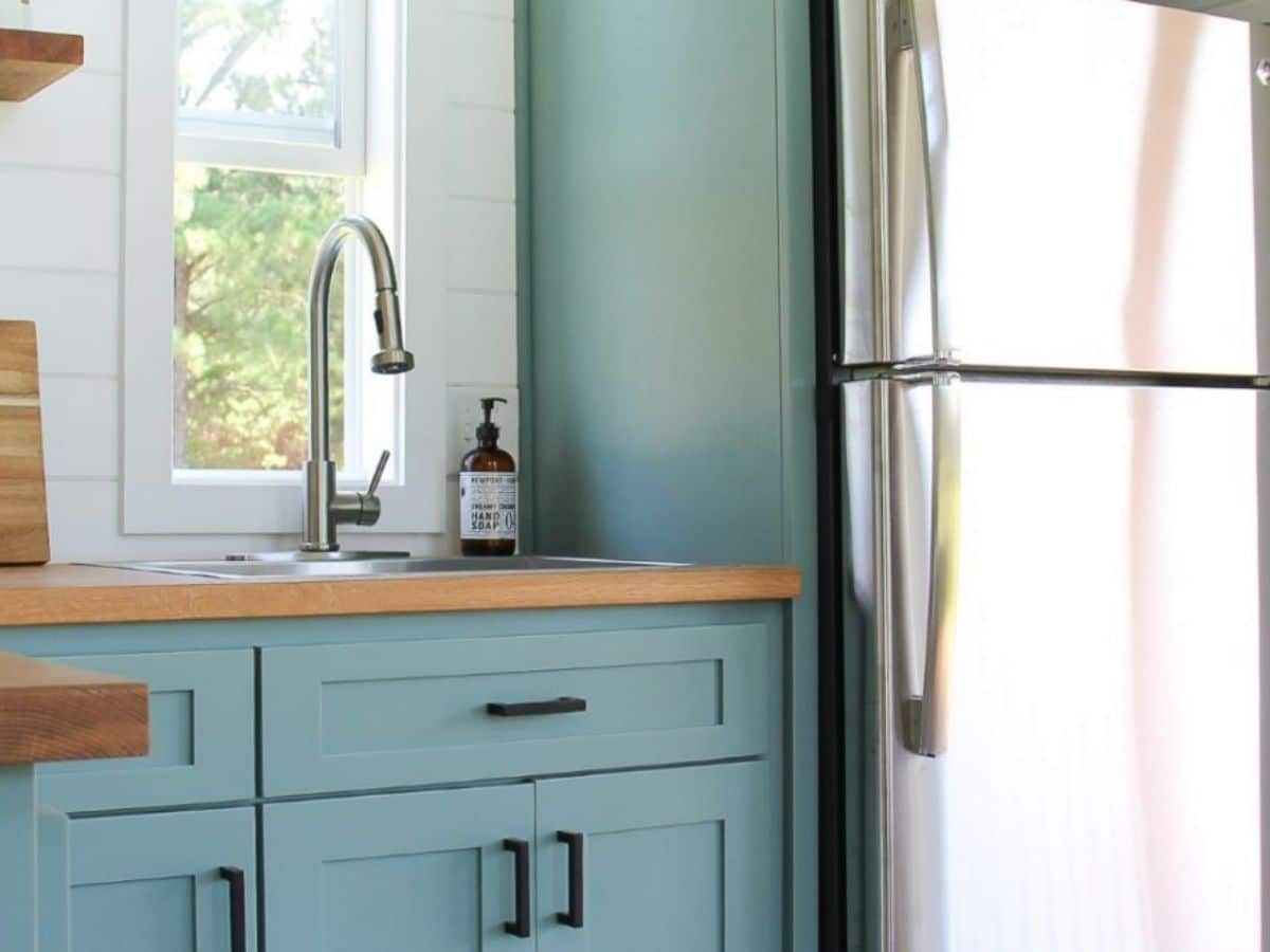Stainless steel refrigerator next to teal cabinet with sink