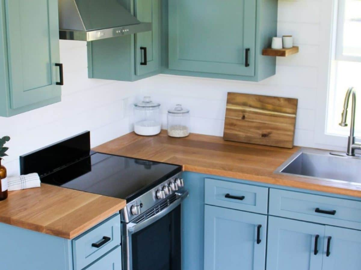Electric flat topped range in butcher block counters in teal kitchen