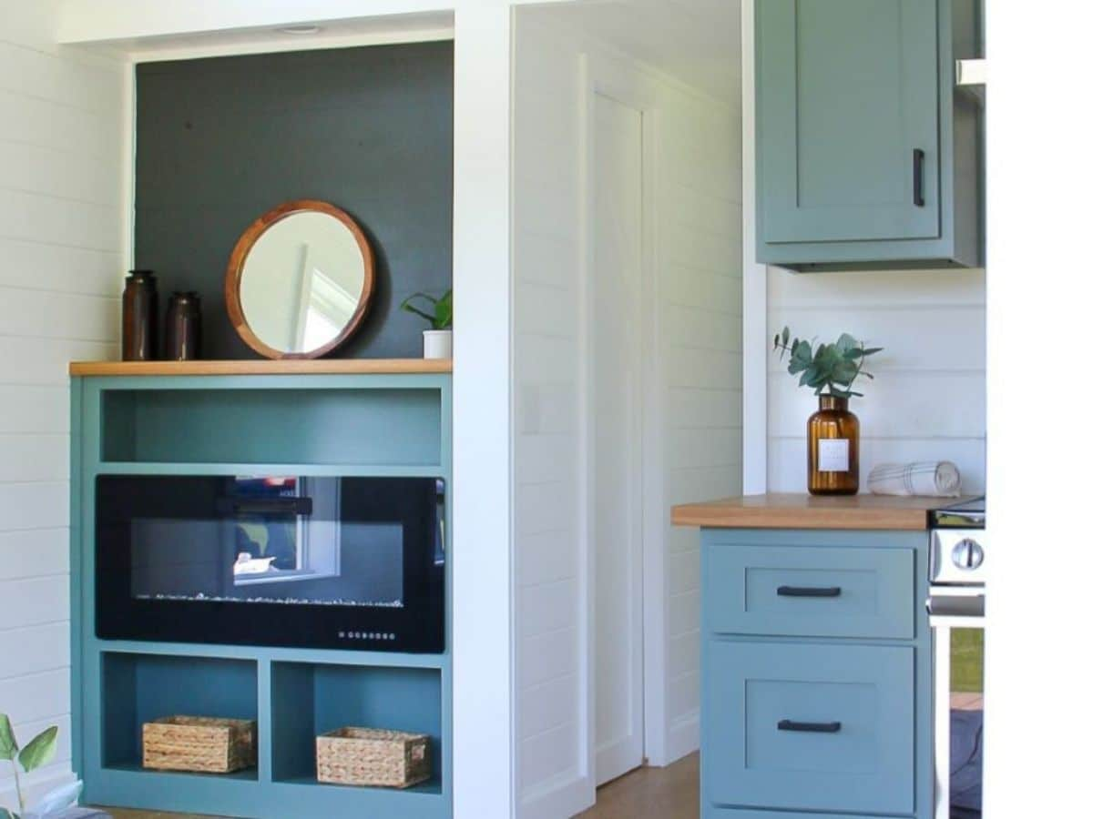 Open teal shelf above fireplace against white wall