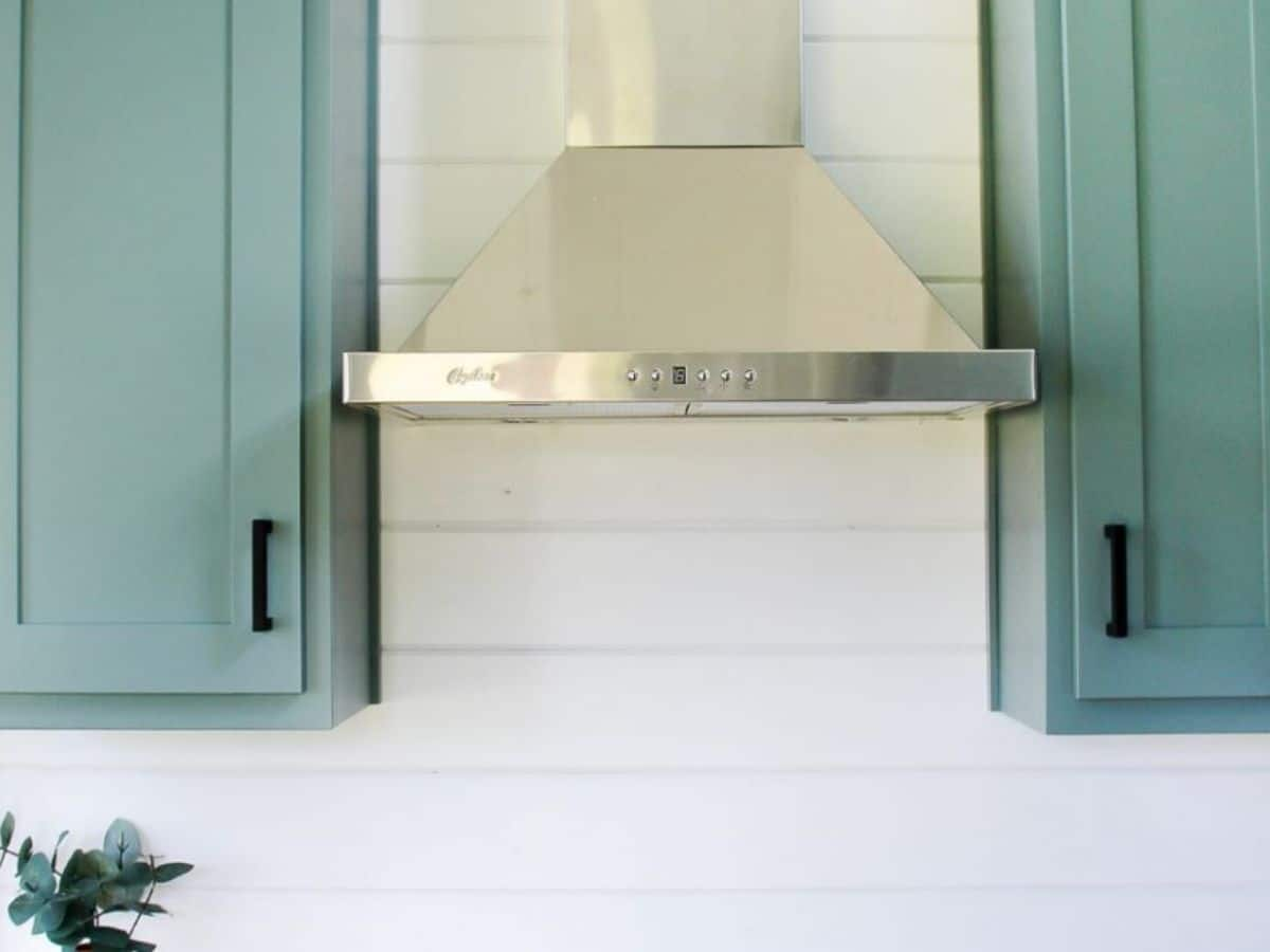 stainless steel vent hood in between teal cabinets