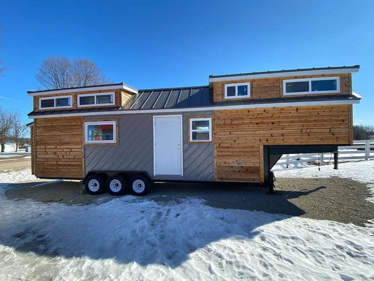 Tiny house on wheels with wood and gray siding and two lofts