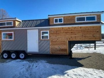 Wood and gray tiny home on lot with snow