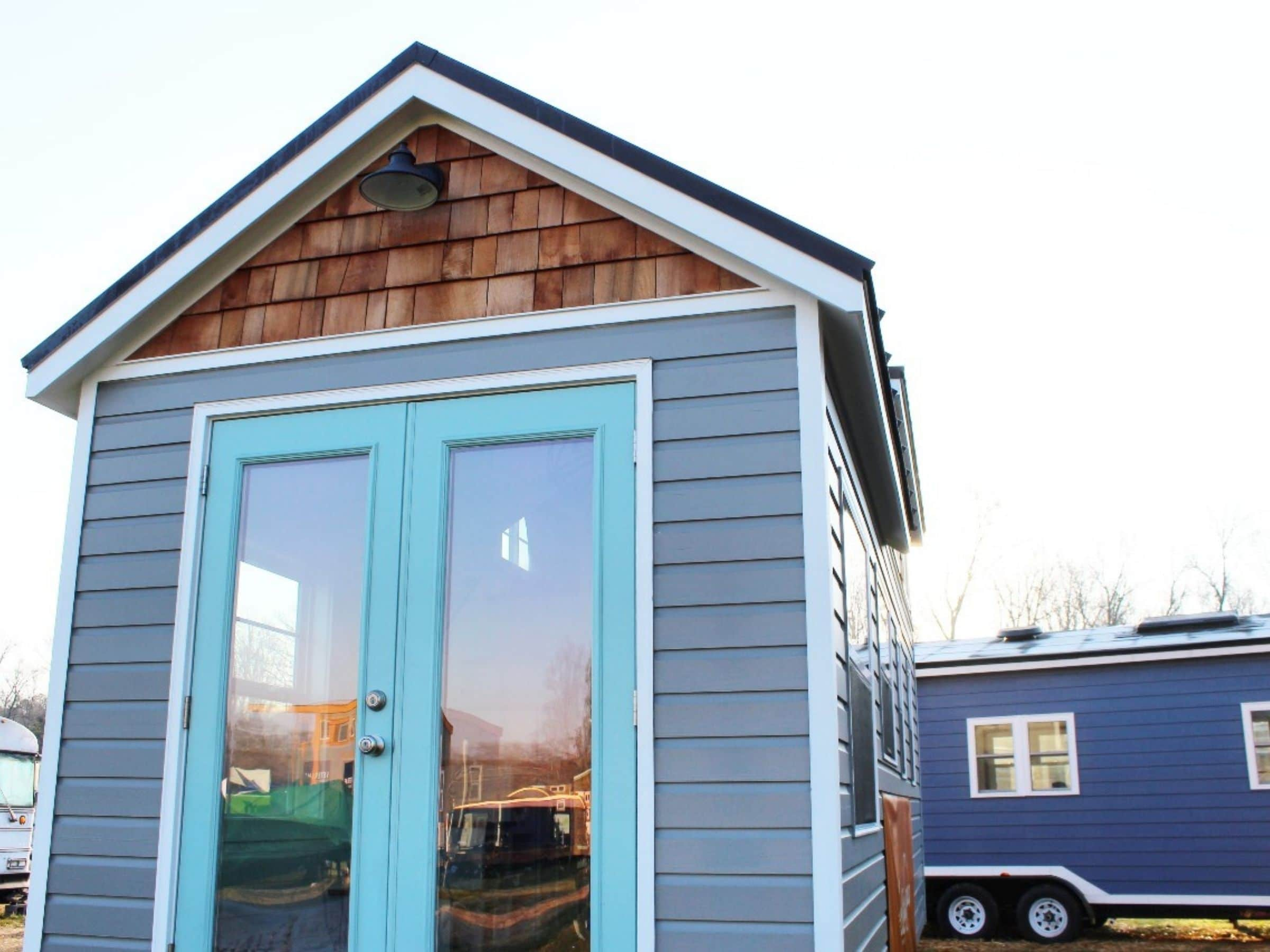 Teal front doors on gray tiny home on wheels