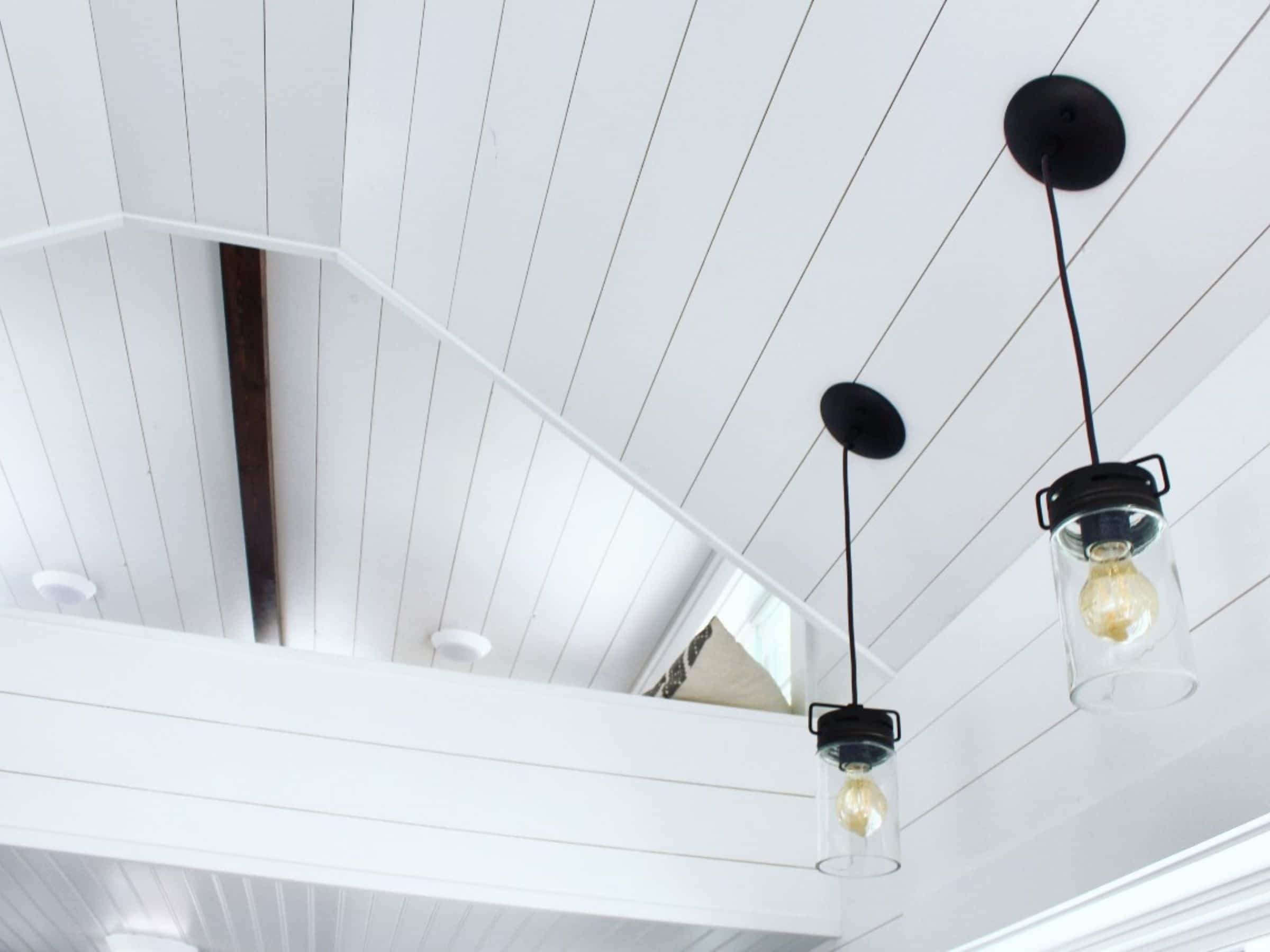 White shiplap ceiling with dangling Edison lights in black fixtures