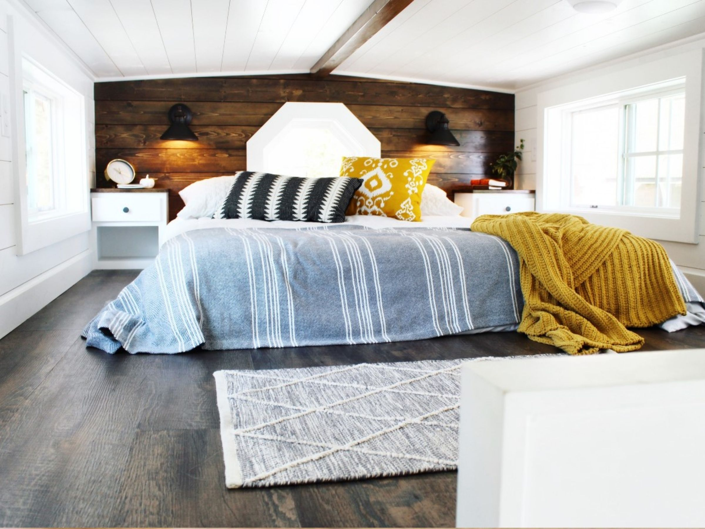 Loft with white and wood walls and mattress against window with pillows and blankets in yellow and blue
