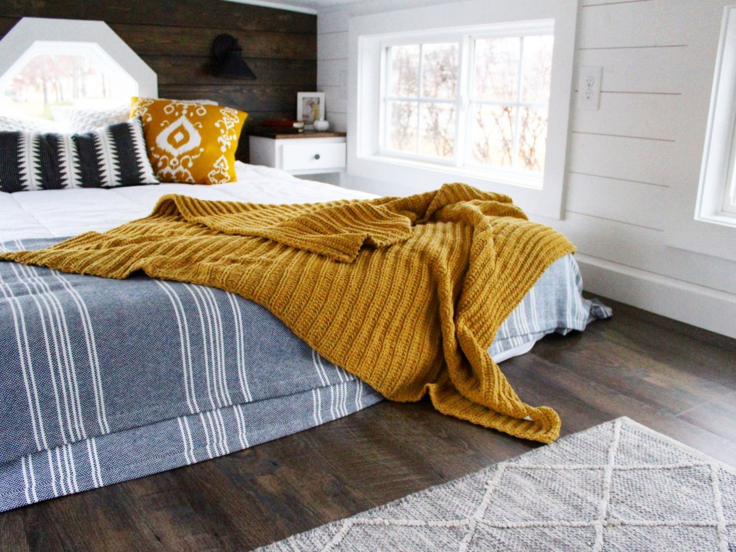 Mattress in loft against wood wall with blue striped blanket