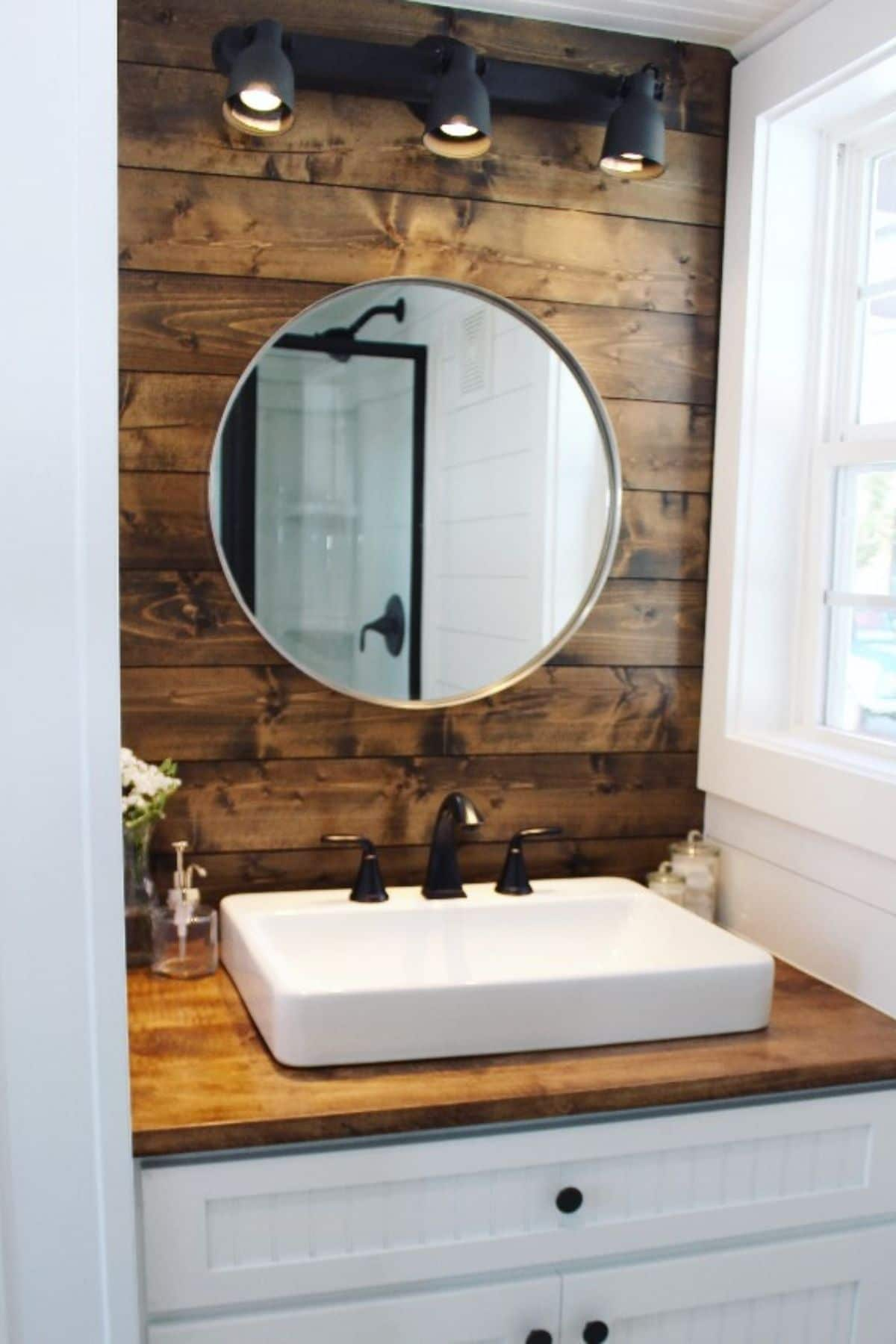 Bathroom sink in woodgrain sink with white cabinet below and round mirror above