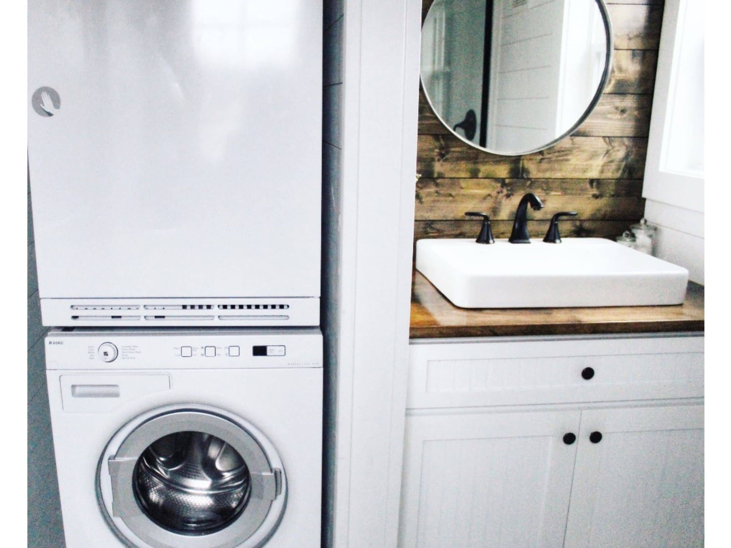 Stacking washer and dryer next to bathroom sink with wood backsplash