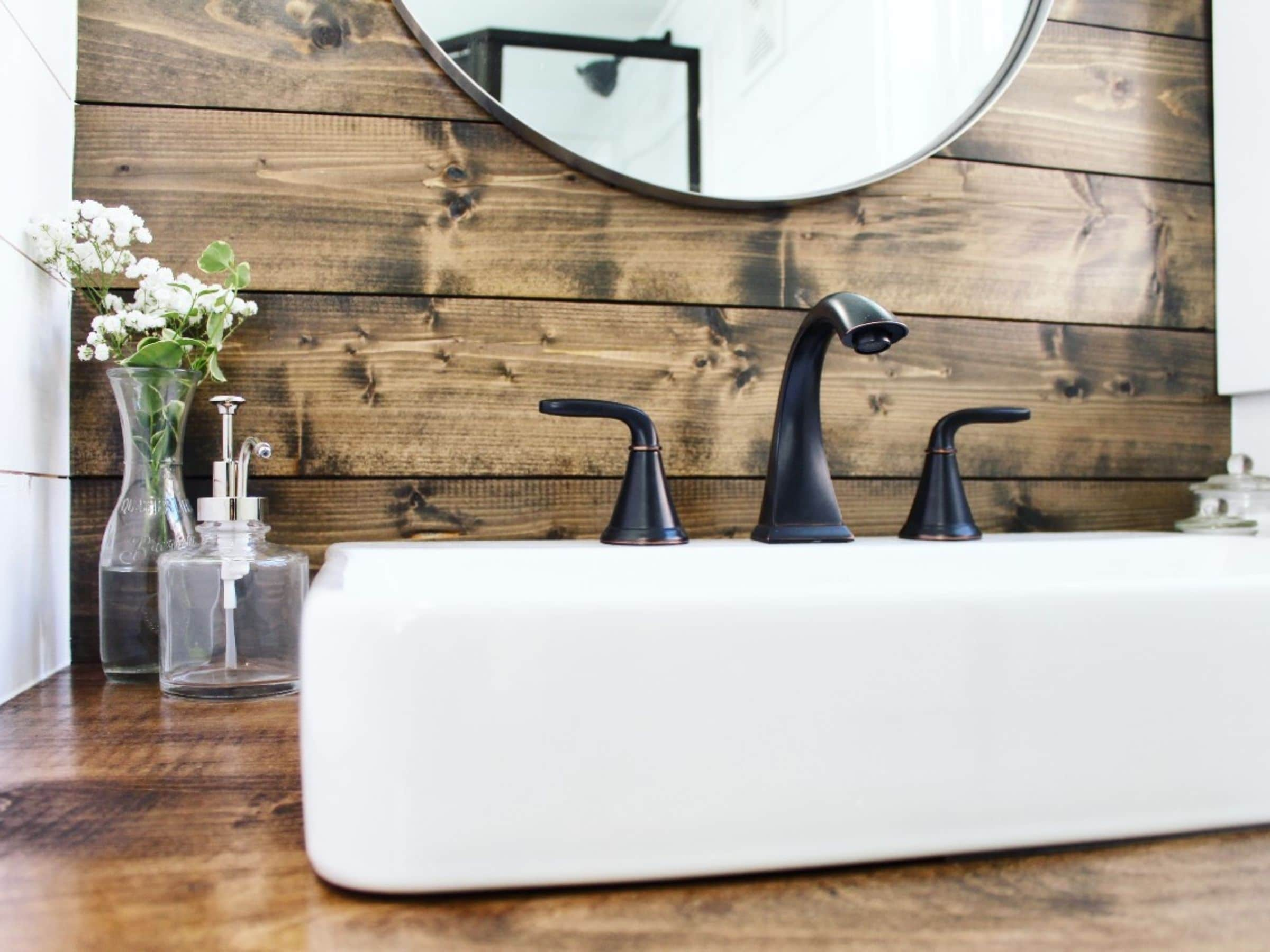 Wood backsplash behind tall white sink with black matte faucet