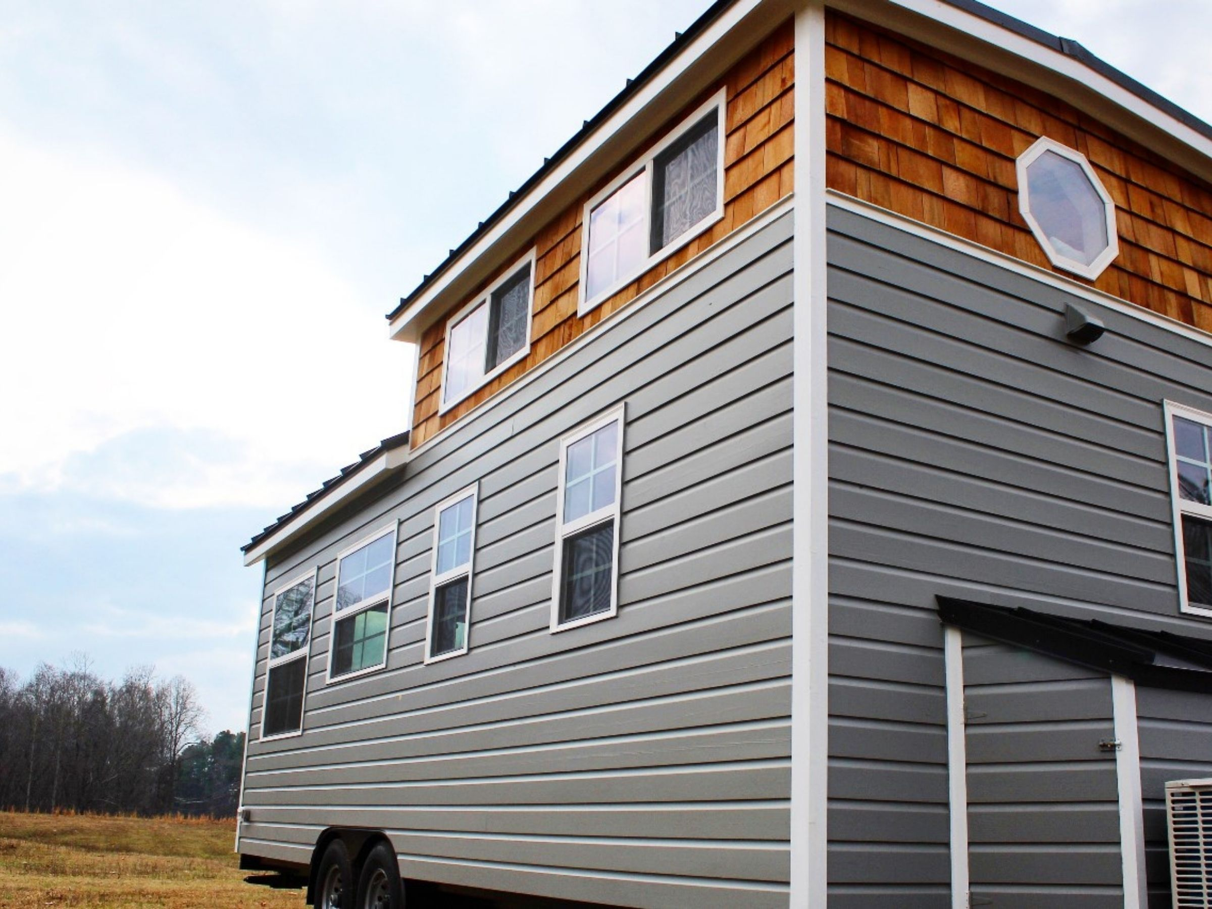 Side of tiny home onw heels with gray siding and multiple windows