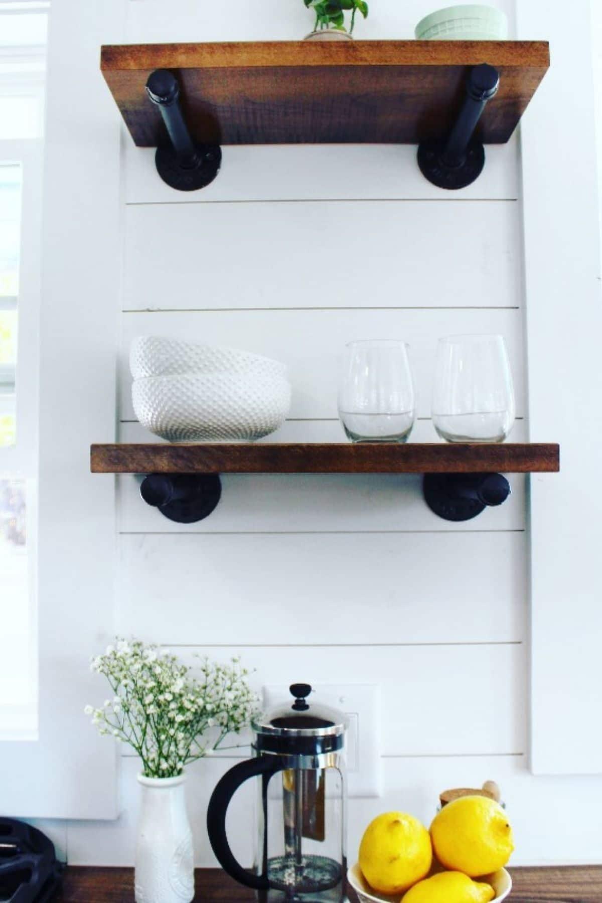 Floating wood shelves on white shiplap wall