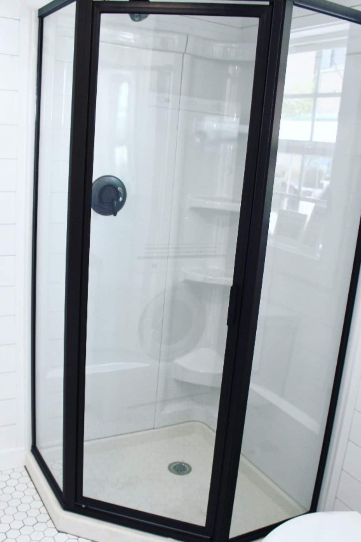 Glass shower stall with black trim