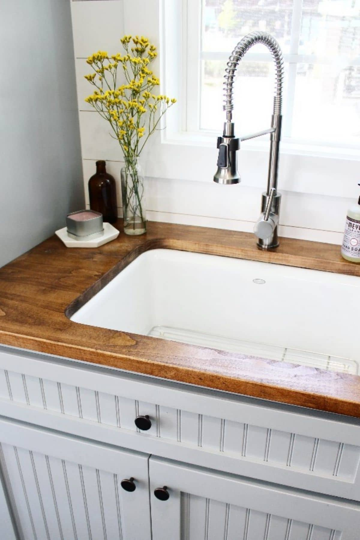 Deep white sink in wood countertop above gray cabinets