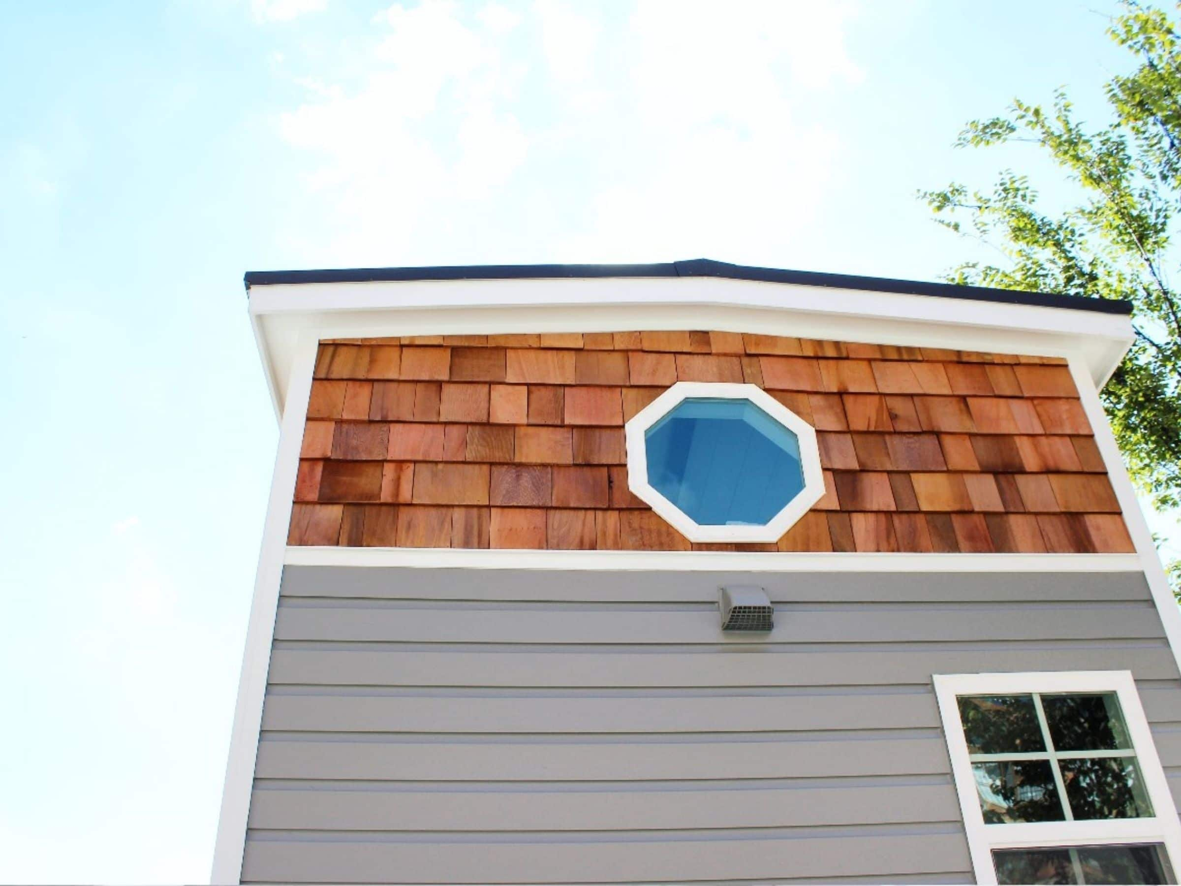 Octagon shaped window in wood siding on back of tiny home