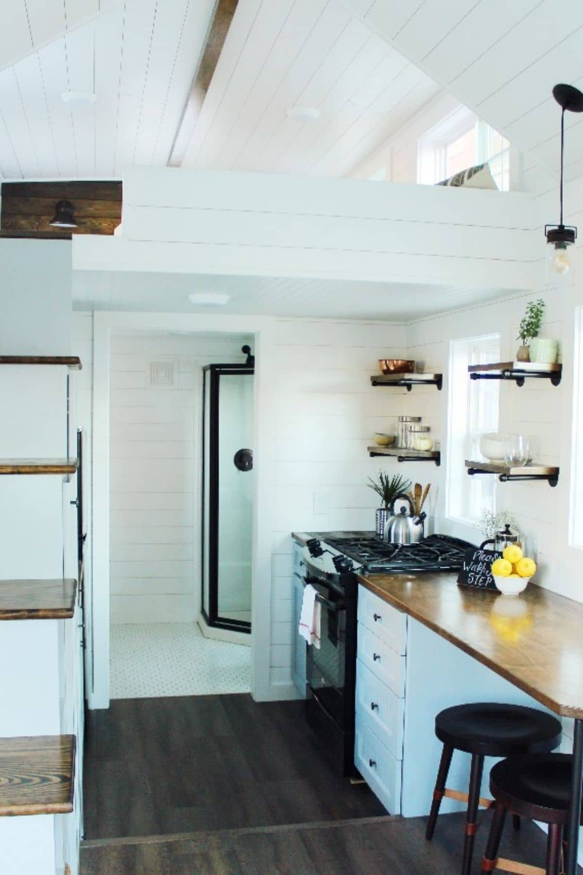 View into kitchen and open bathroom door in light tiny home