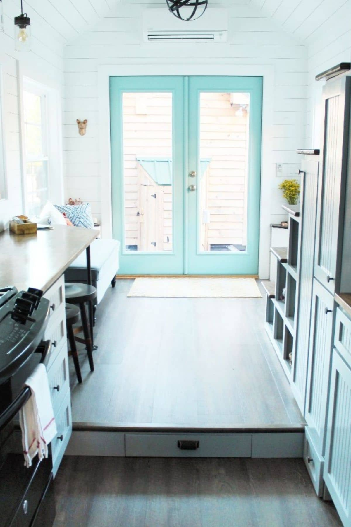 View of teal french doors from inside tiny home