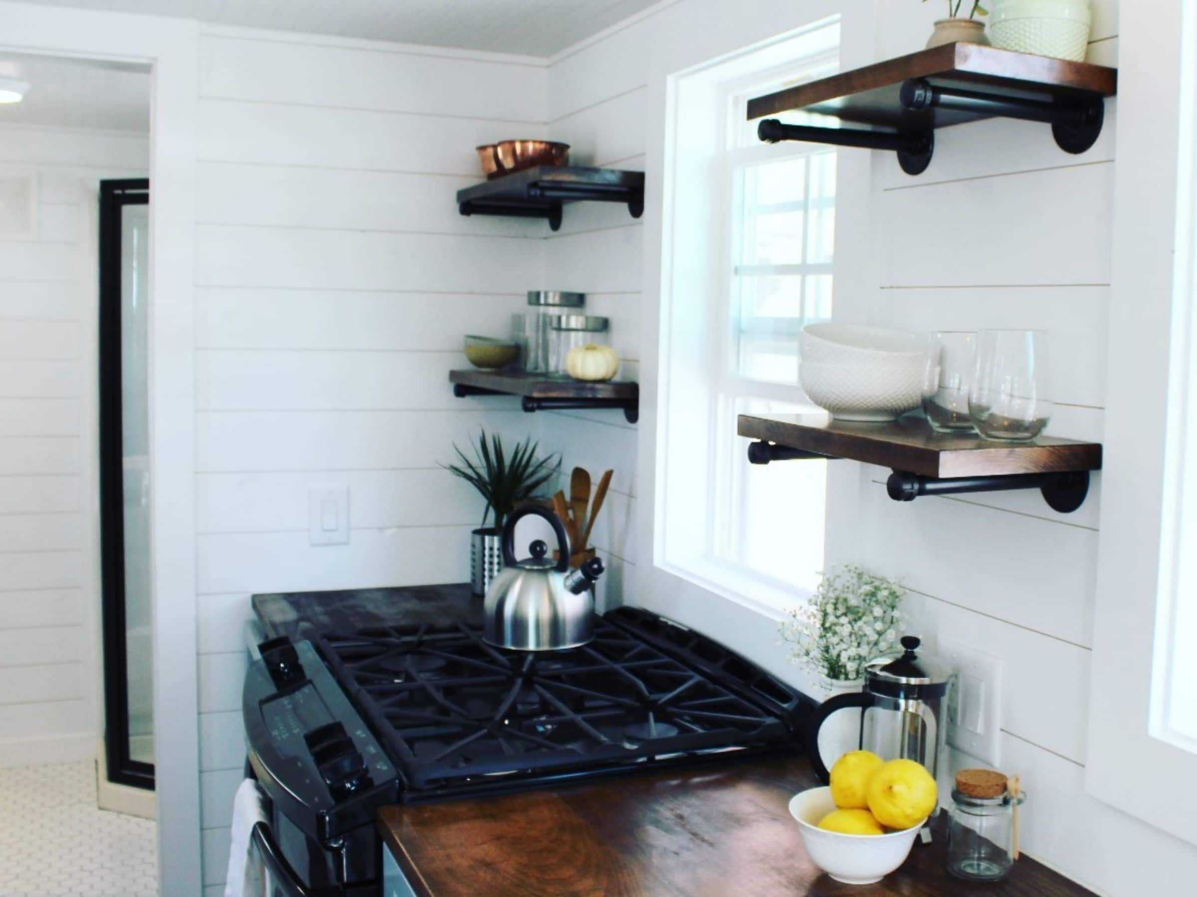 Kitchen counter with black top gas stove under window