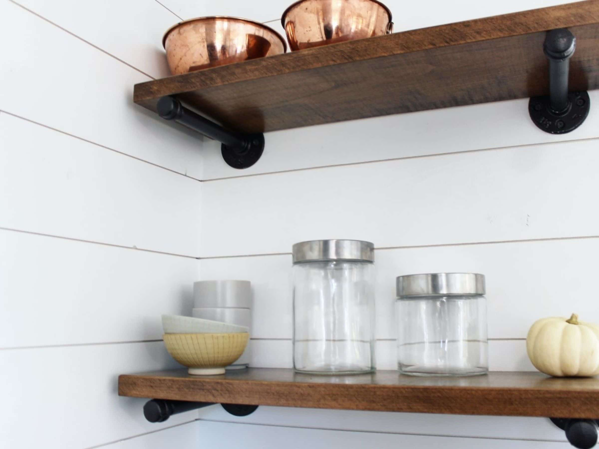 Wooden floating shelves on white shiplap wall holding copper bowls