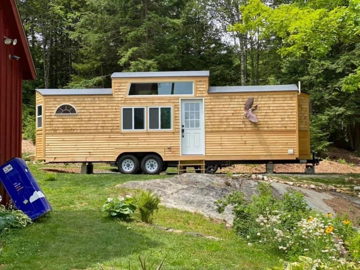 Tiny house with middle loft and wood siding on lot