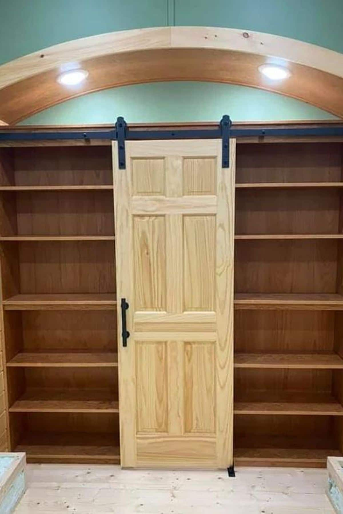 Wooden barn door hanging between bookcases against arched green wall
