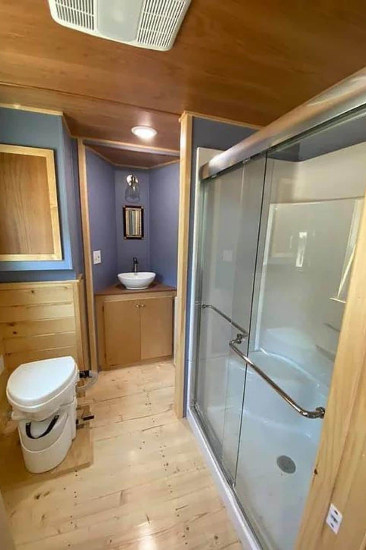 Wood bathroom with blue walls and glass shower on right with compost toilet on left