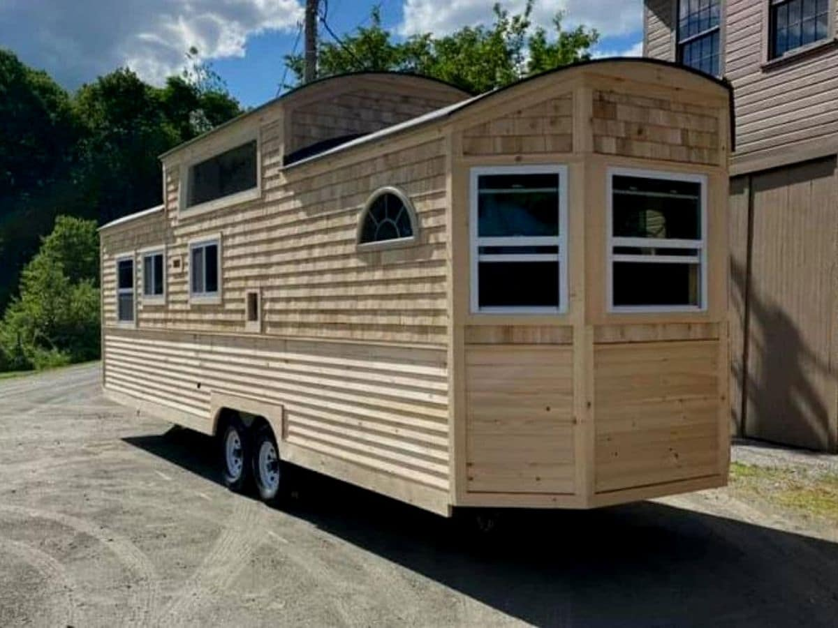 End of tiny house with wood siding and large windows