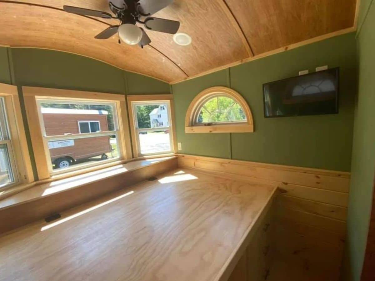 Platform bed against window in room with green walls
