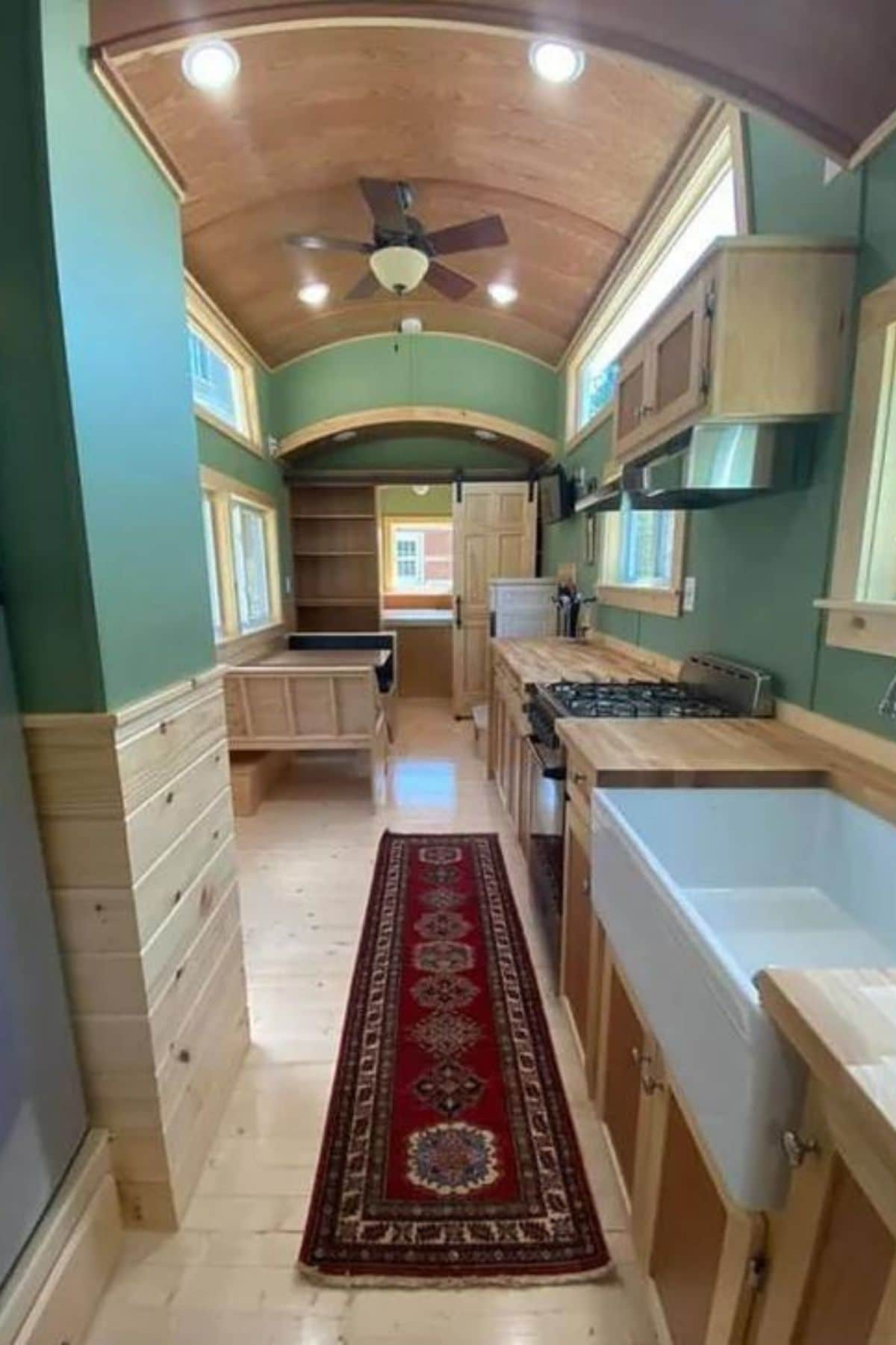 View into tiny house kitchen with white sink and gas stove
