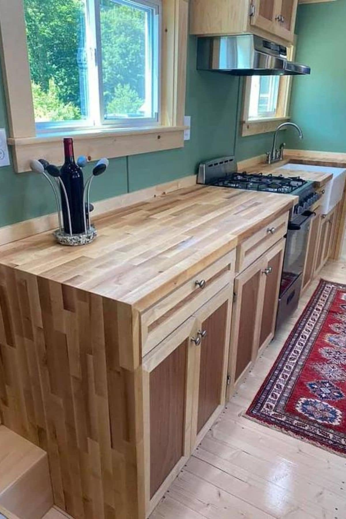 Two tone wood slat cabinets in kitchen against green wall