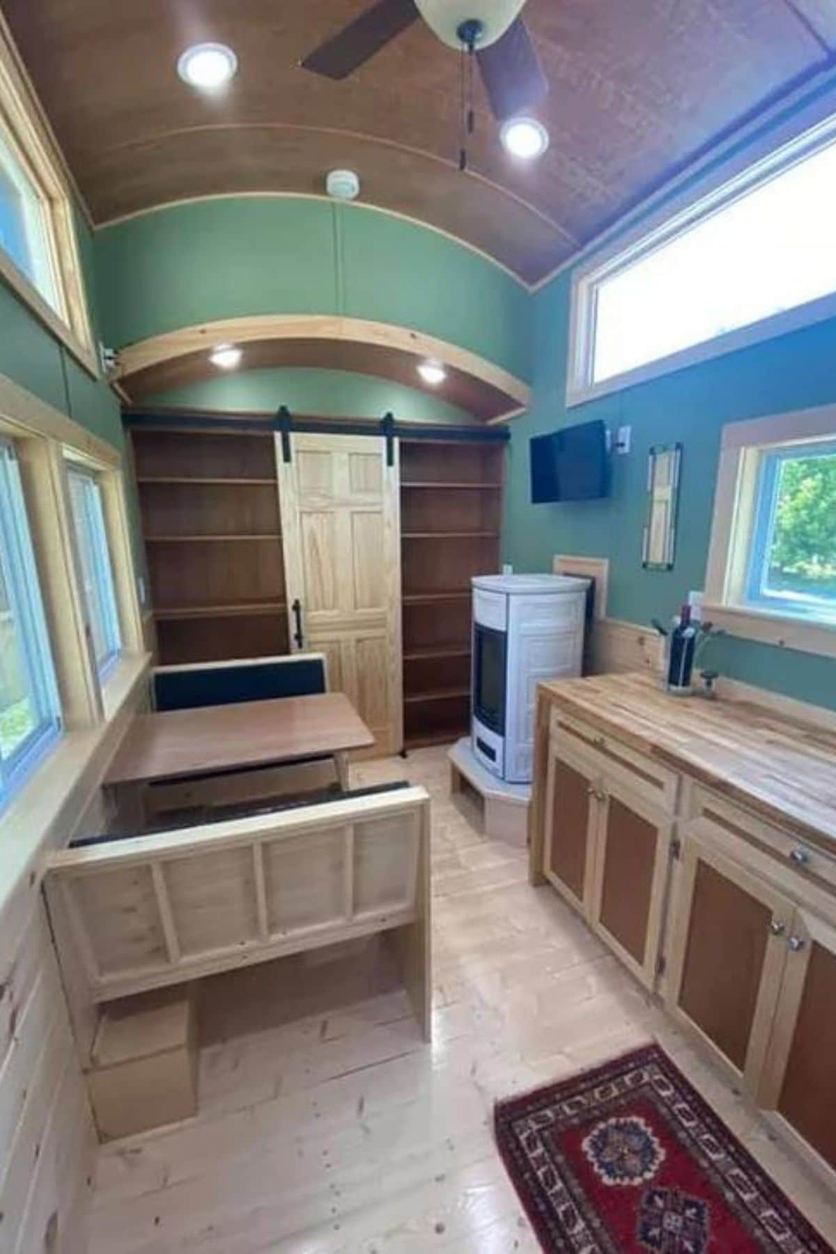 View to end of tiny home showing white stove on right side and booth on left side