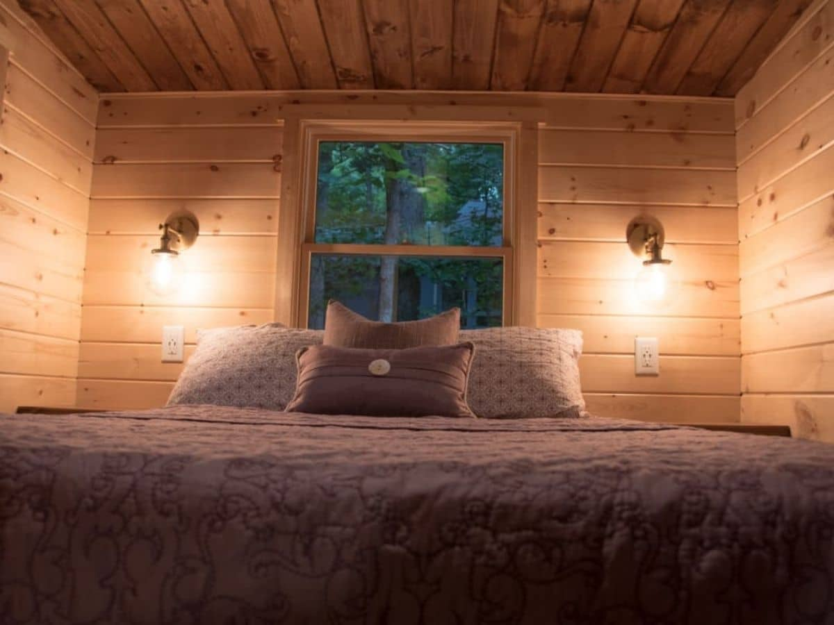 Bed against window in loft with two lights on walls