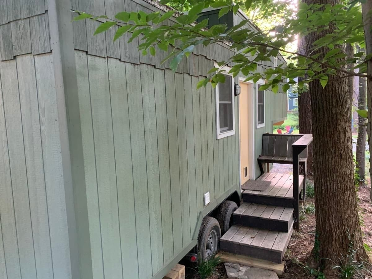 Small porch on front of green tiny home on wheels