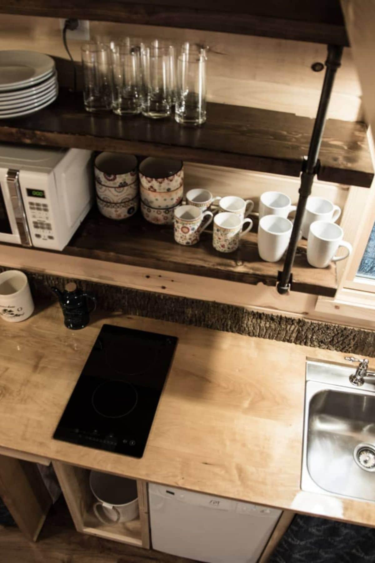 Butcher block counter with 2 burner electric cooktop below shelves