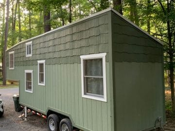 Two tone green tiny house on wheels next to forest