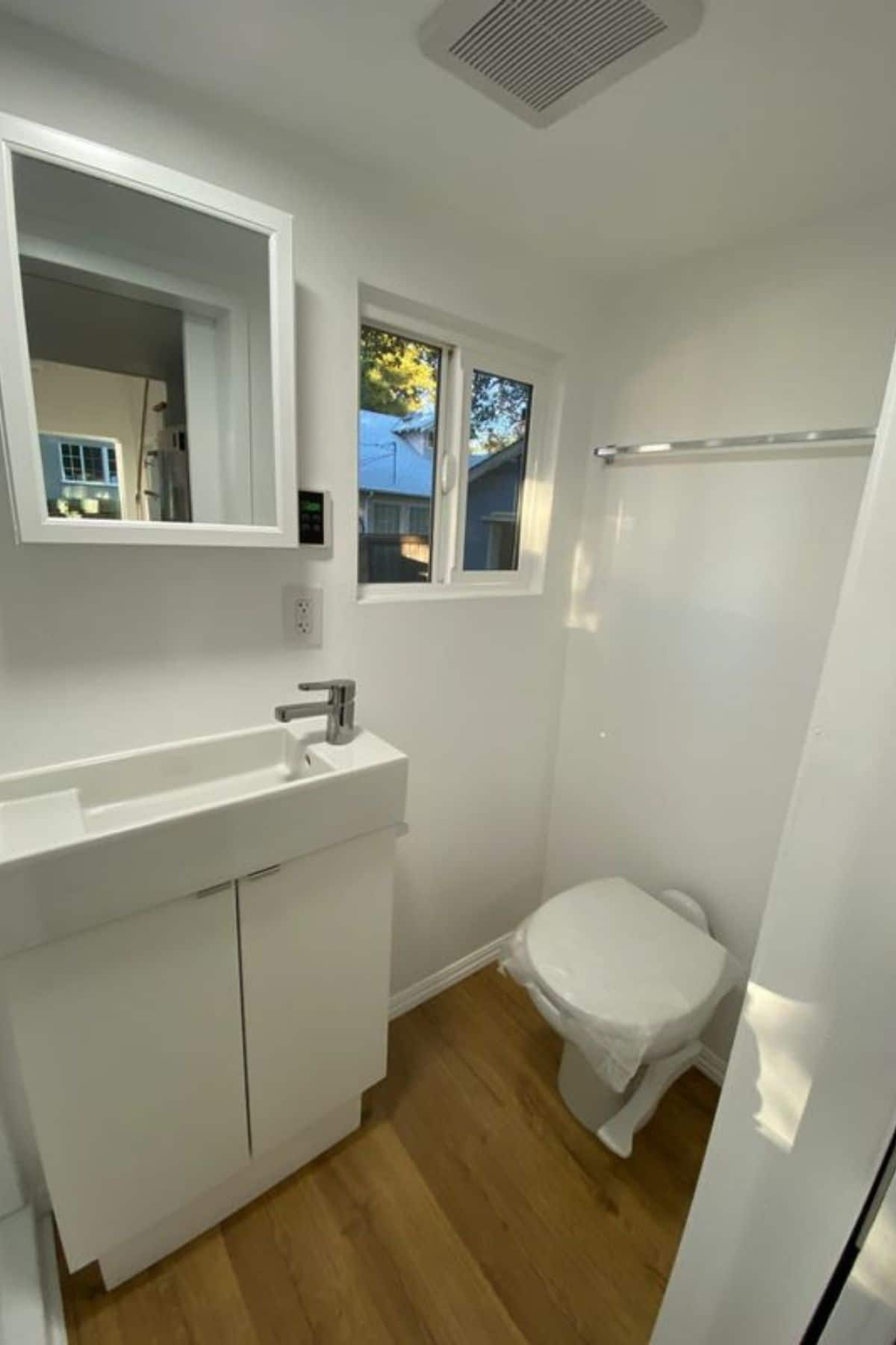 white vanity with medicine cabinet above and compost toilet to right