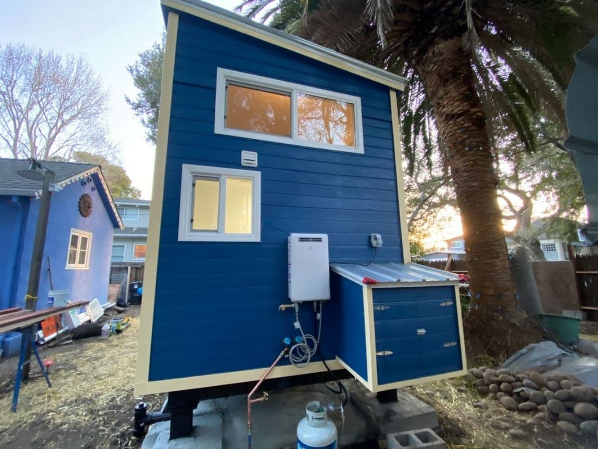 end of blue tiny house showing exterior box storage