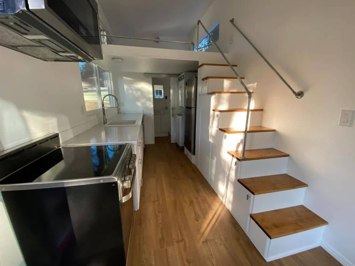 Kitchen of tiny home with white stairs to loft on right and stove on left