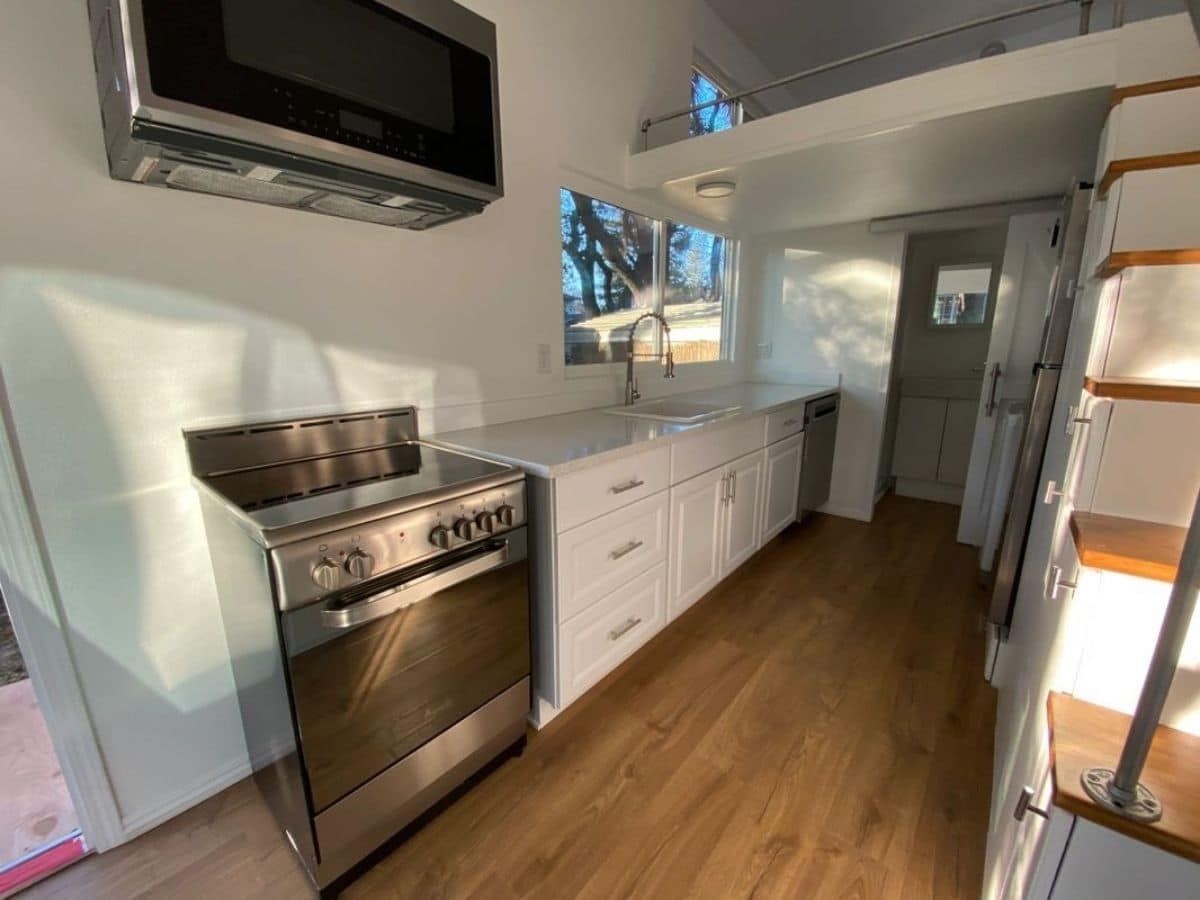 stainless steel full sized range against white counters in tiny kitchen