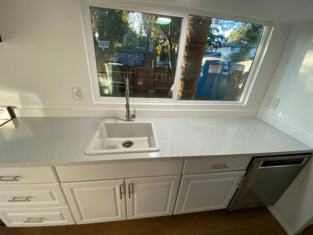 white countertop above white counters in kitchen with dishwasher at end