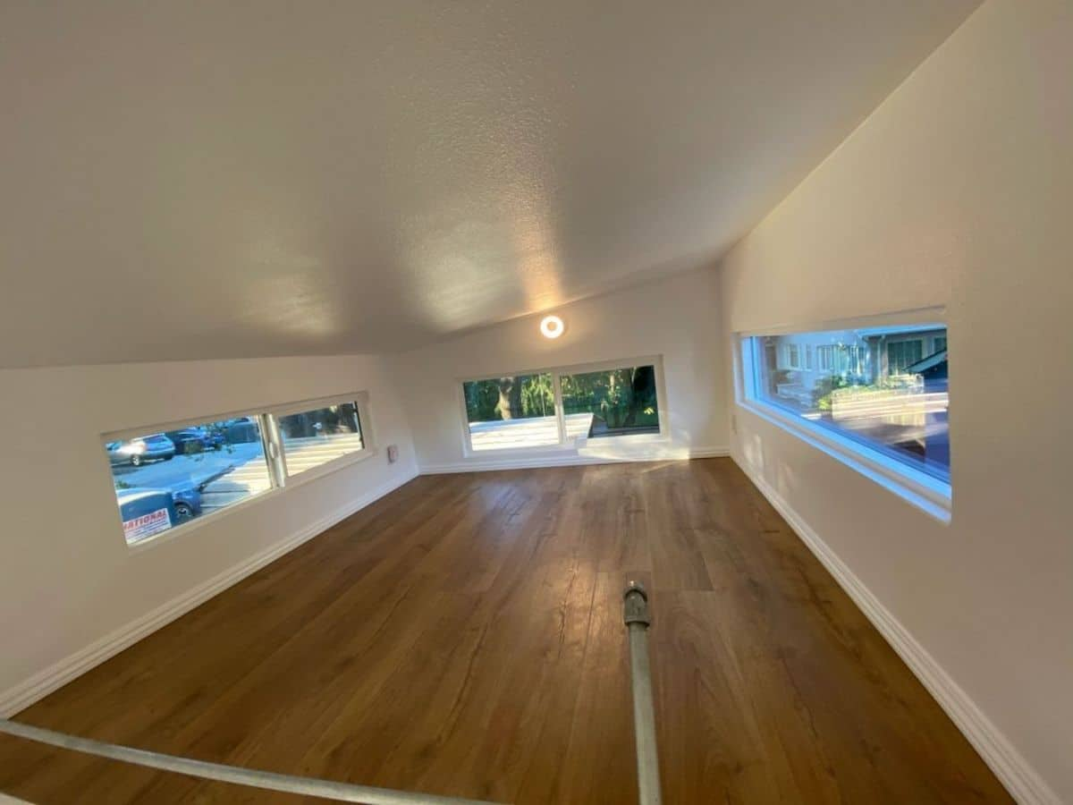 deep loft with white walls and wood floor with three windows