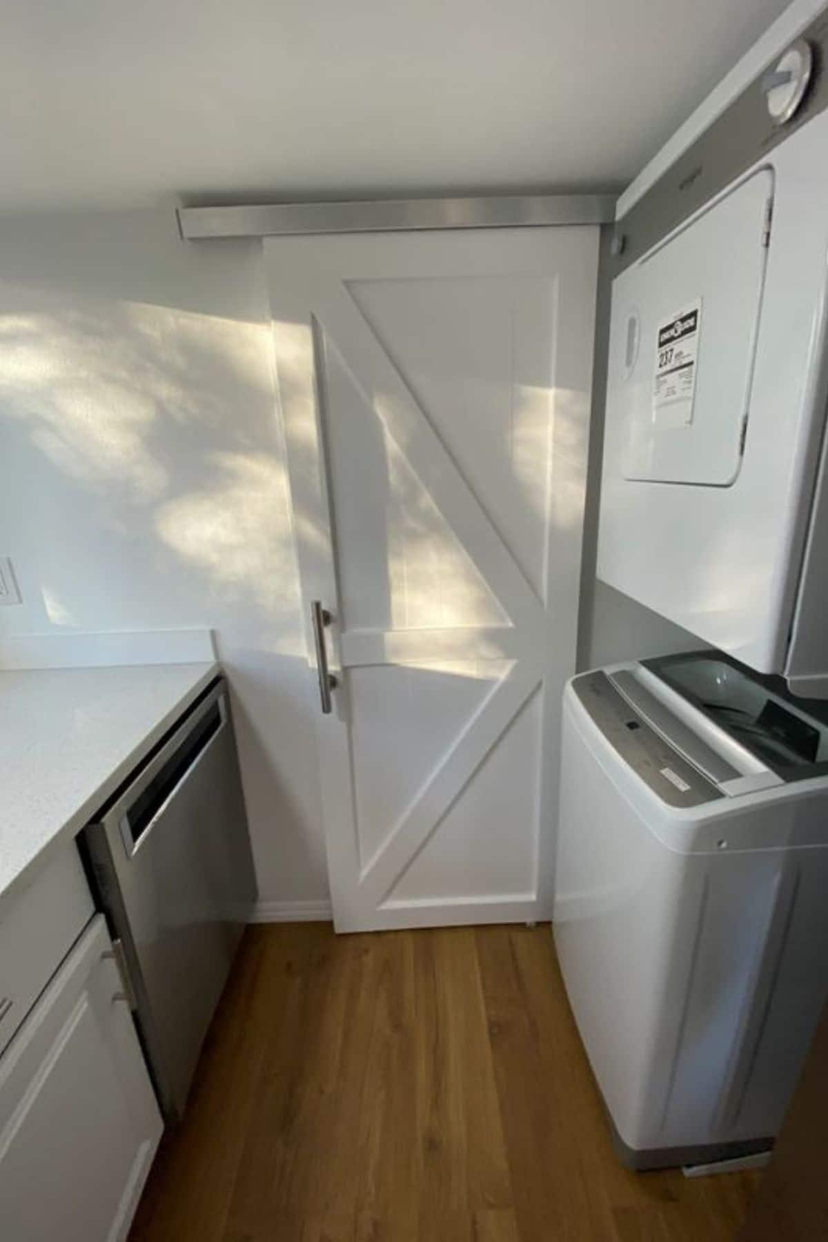 barn door to bathroom next to laundry setup on right