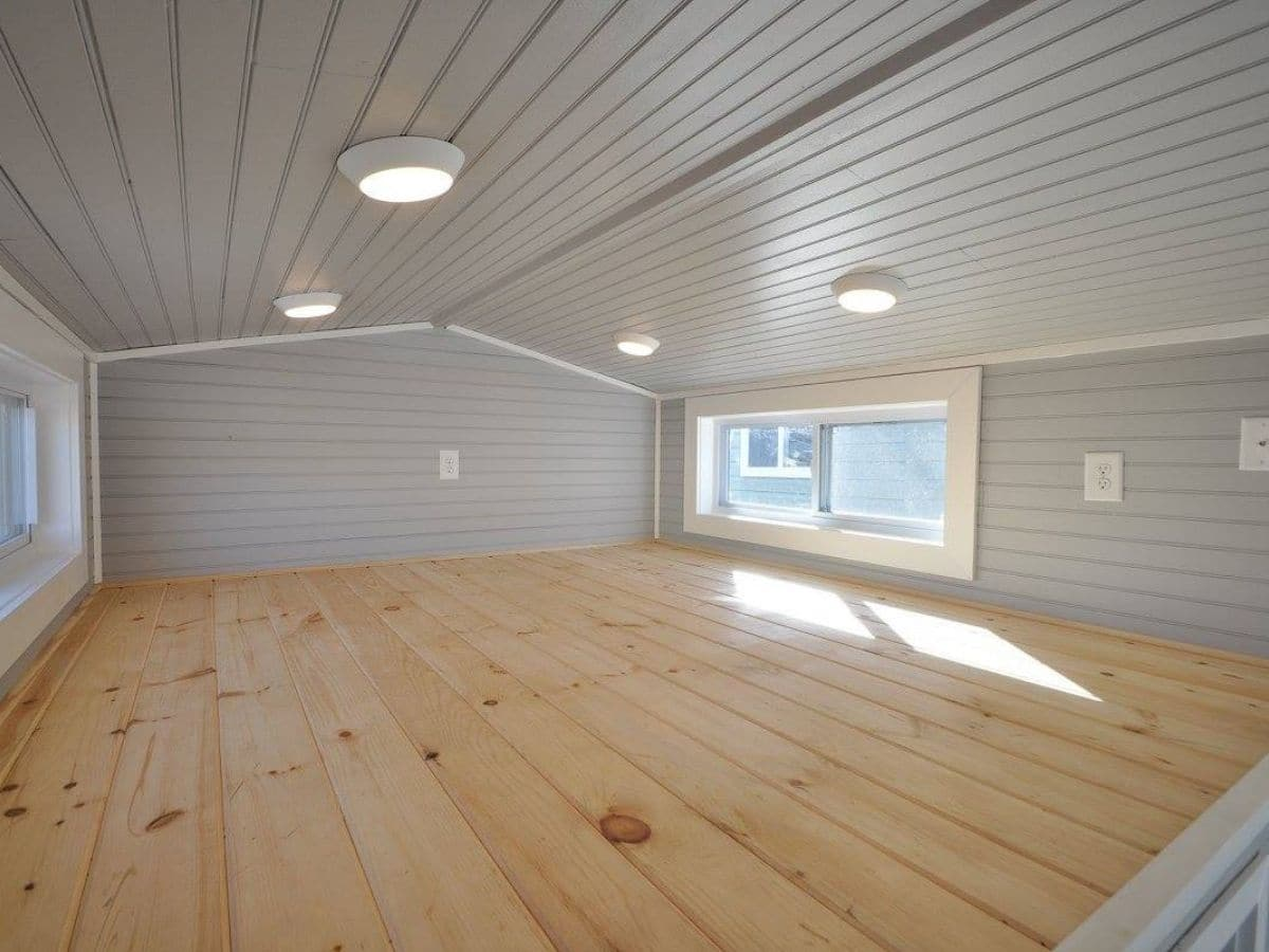 Tiny home loft with wood floors and gray walls and ceiling with window on right side