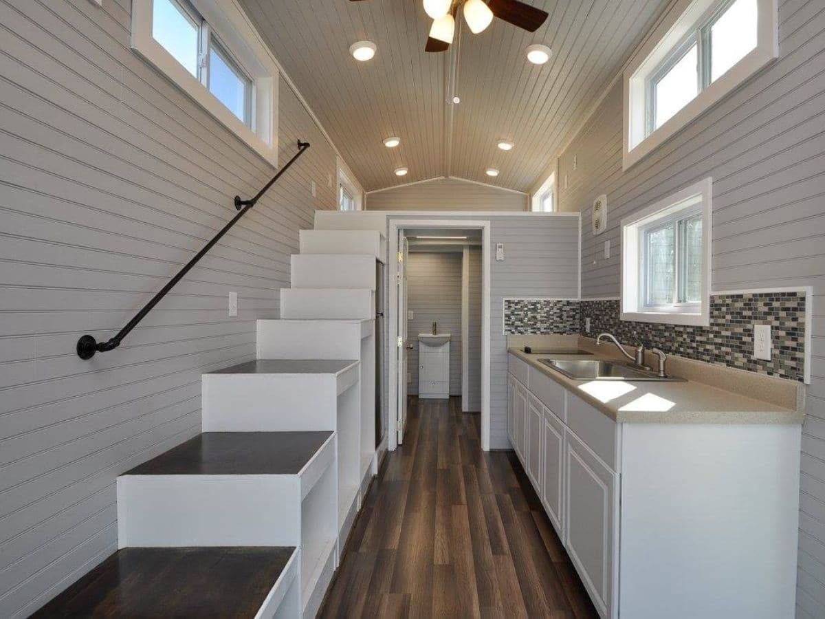 Stairs to loft on left with metal rail against wall and kitchen counter on right