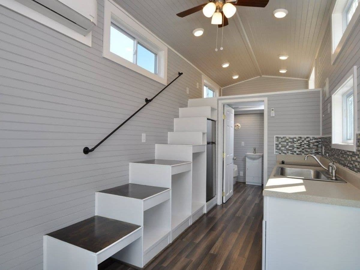 Open cubbies under stairs with wood tops on left of image