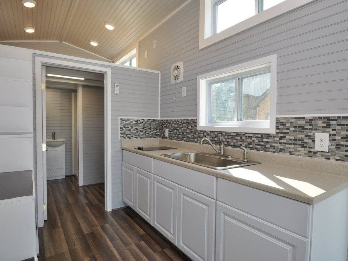 White cabinets with wood counter and tile backsplash