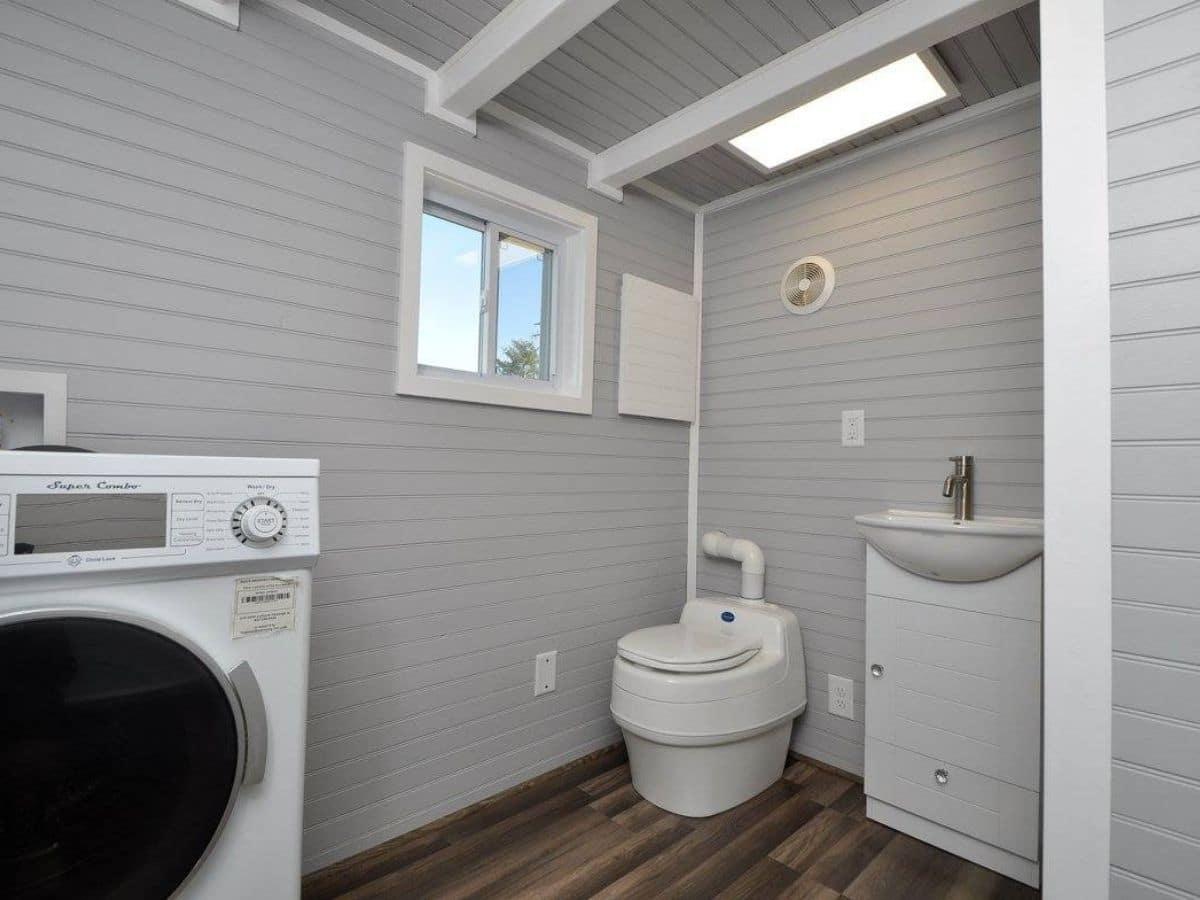 White compost toilet next to white vanity against gray walls