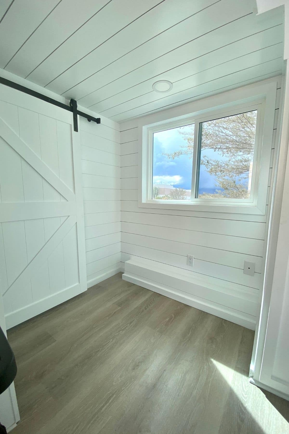 White barn door on right side of image with two windows on white wall to left