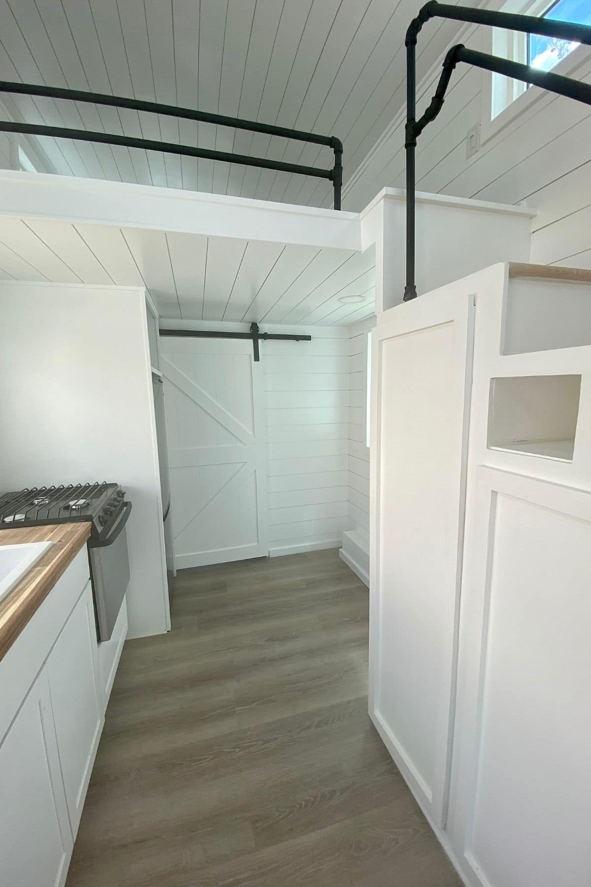 View into bathroom from kitchen with white cabinets under stairs to left